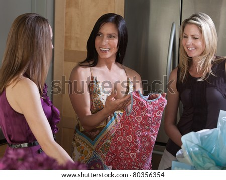 Happy pregnant woman holds baby clothes with friends in kitchen - stock photo