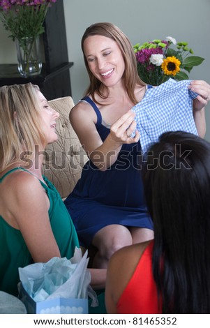 Happy pregnant woman holds gift of baby clothes - stock photo