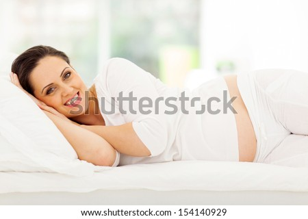 happy pregnant woman lying on bed at home