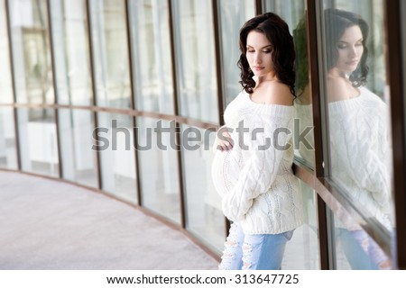 Happy pregnant woman outdoors in park. healthy pregnancy. Young pregnant girl posing in street in woolen sweater.