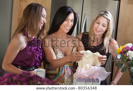 Happy pregnant woman receives baby clothes as gift from her friend - stock photo