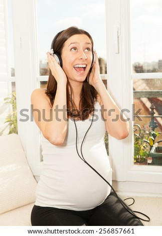 happy pregnant woman singing and listening to music - stock photo
