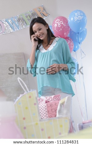Happy pregnant woman using cell phone at a baby shower