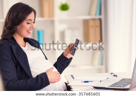 Happy pregnant woman watching ultrasound while working in the office - stock photo