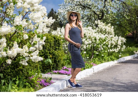 Happy pregnant woman wearing hat and sunglasses - stock photo