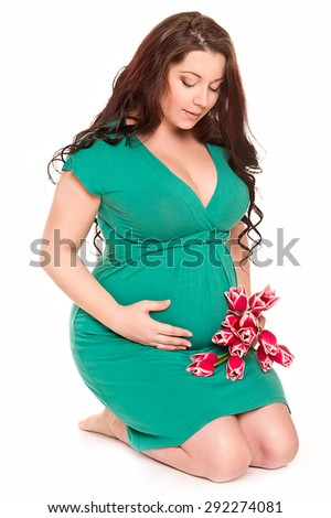 Happy pregnant woman with bouquet tulips - stock photo