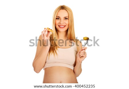 Happy pregnant woman with cake and pickles - stock photo