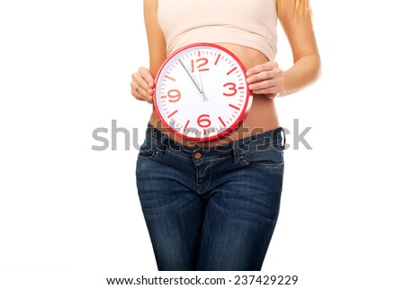 Happy pregnant woman with clock expecting baby - stock photo