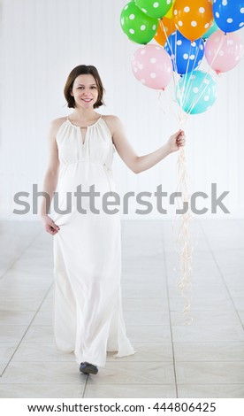 Happy pregnant woman with colorful balloons