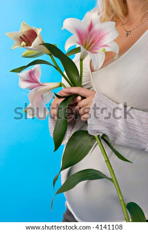 happy pregnant woman with lily in hands - stock photo