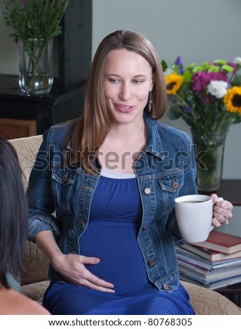 Happy pregnant woman with mug on a chair - stock photo