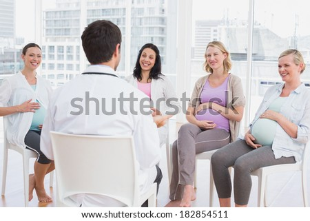 Happy pregnant women listening to doctor at antenatal class at the hospital - stock photo