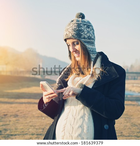 Happy pregnant young Caucasian woman with smart phone outdoors smiling. Cute young mom expecting a baby walking outdoors using smart phone wearing coat and knitted hat. - stock photo