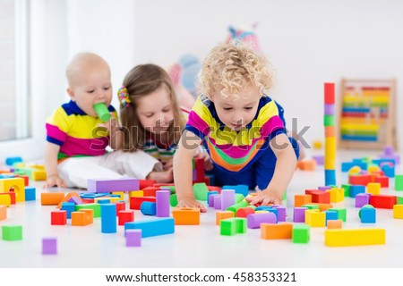 Happy preschool age children play with colorful plastic toy blocks. Creative kindergarten kids build a block tower. Educational toys for toddler or baby. Siblings having fun playing together. - stock photo