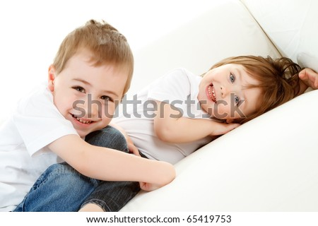 Happy preschool boy and baby sister relaxing on white background.