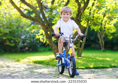 Happy preschool boy riding his first bike on warm summer day. - stock photo