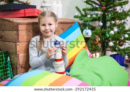 Happy preschool Caucasian girl with a gift in hand next to Christmas tree - stock photo