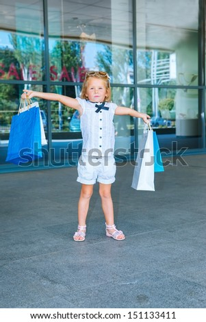 Happy preschool girl holding gift bags in front of the shopping center - stock photo