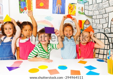 Happy preschool group of little kids, boys and girls diverse looking holding cardboard color shapes by the table in the kindergarten with decoration and drawings on background