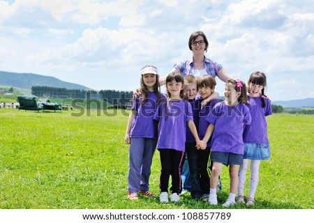 happy preschool  kids group have fun and play game  on outdoor classes in nature - stock photo