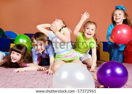 Happy preschool kids playing with balloons - stock photo