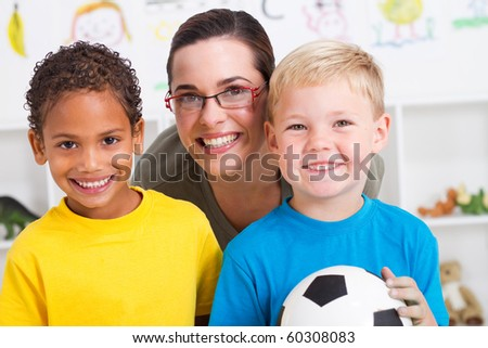 happy preschool teacher and two boys in classroom - stock photo