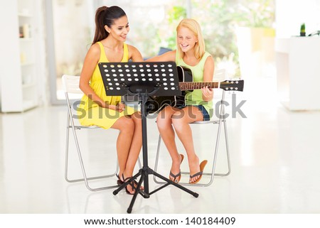 happy preteen girl having guitar lesson with music tutor at home - stock photo