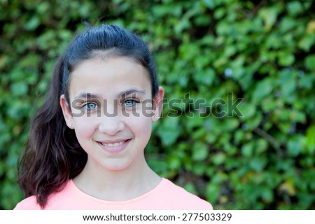 Happy preteen girl with blue eyes smiling at outside - stock photo