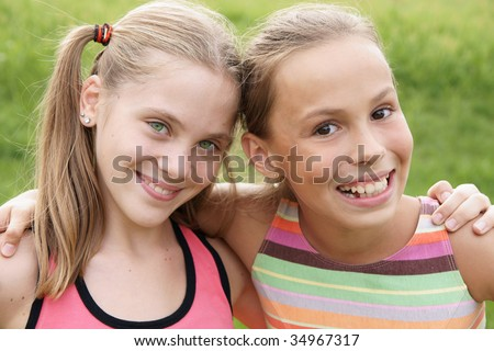 Happy preteen girls friendly hugging on green grass background - stock photo