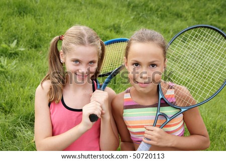 Happy preteen girls in sport outfits with tennis rackets on green grass background