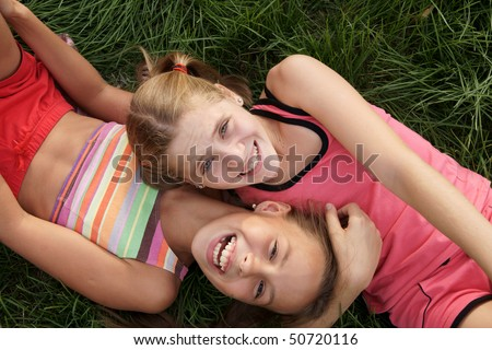 Happy preteen girls lying and playing on green grass - stock photo