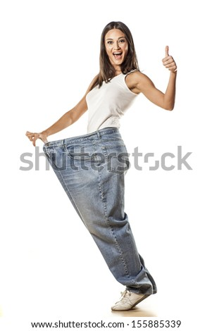 happy pretty attractive girl posing in huge pants with the thumbs up - stock photo