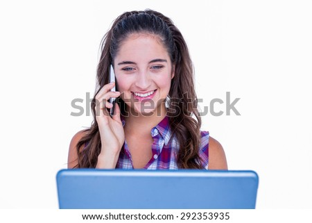 Happy pretty brunette using tablet computer and having phone call on white background - stock photo