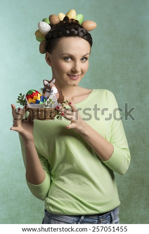 Happy, pretty brunette woman with funny hairstyle with eggs and easter basket filled by decorations. She wears green blouse. - stock photo