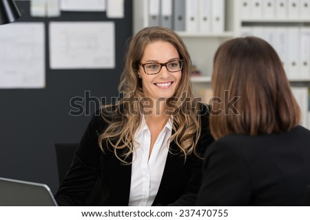Happy Pretty Corporate Woman with Long Blond Hair Talking Business Matters to Co-worker at the Office. - stock photo