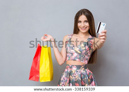 Happy pretty excited female shopper with long hair showing a credit card, holding colourful bags and smiling - stock photo