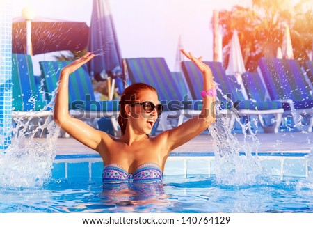 Happy pretty girl having fun in the pool, cute playful female splashing water in swimming pool, relaxation and play in poolside, summer vacation concept - stock photo