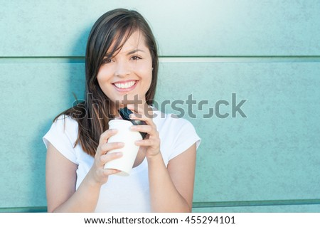 Happy pretty girl holding cup of takeaway coffee smiling on green wall with copy text space - stock photo