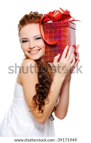 Happy pretty girl holding present close her head over white background - stock photo