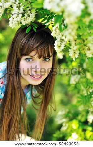 happy pretty girl standing  near blossom of  acacia - stock photo