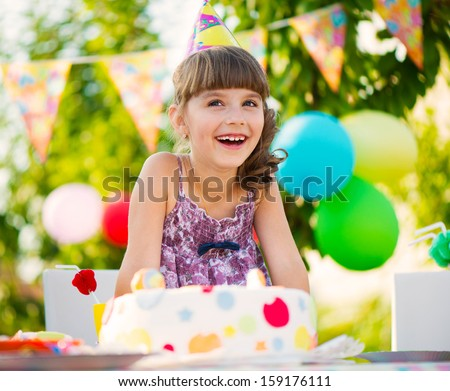 Happy pretty girl with cake at birthday party - stock photo
