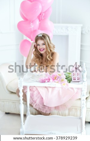 Happy pretty girl with cream cake and pink balloons at birthday party.  Barbie style. Princess. Smiling kid with tiara crown - stock photo