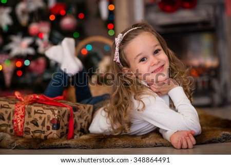 Happy pretty girl with gift box lies near Christmas tree in the room of the house.  Merry Christmas and New Year. - stock photo