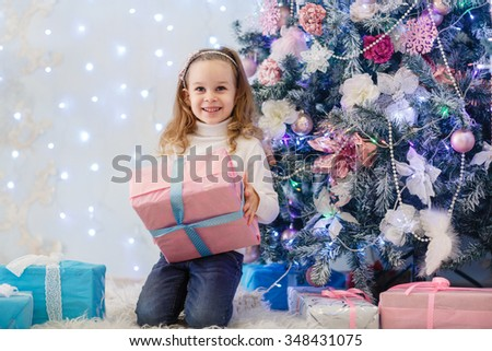 Happy pretty girl with gift boxes sits near Christmas tree in the room of the house.  Merry Christmas and New Year. - stock photo