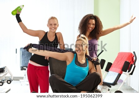 Happy pretty girls posing at the gym. - stock photo