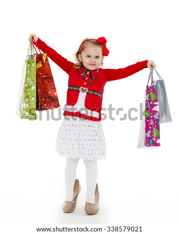 Happy pretty little child with shopping bags stands on a white background. 3 year old. - stock photo