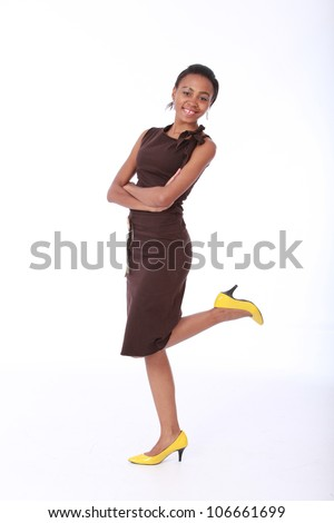 Happy pretty smiling young African American business woman or colleague wearing a professional brown dress and yellow shoes with arms crossed and foot kicked behind isolated on a white background