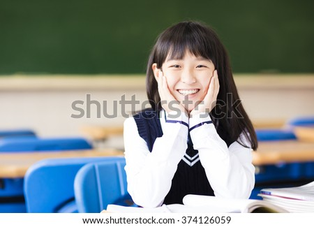 happy pretty  student girl with books in classroom - stock photo