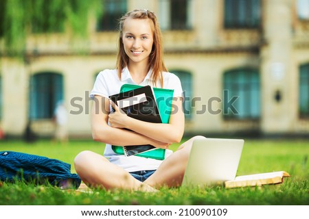 Happy pretty student woman is sitting on the lawn in the university campus with notebook in her hands and using laptop. Study outdoors concept.