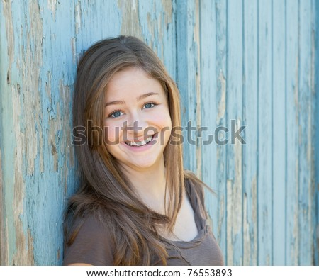 Happy, Pretty Teen Girl Leaning on Rustic Blue Wall - stock photo